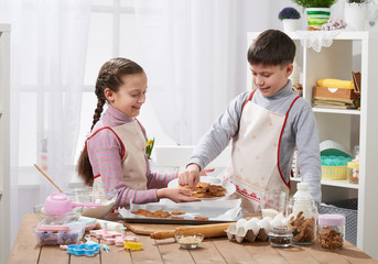 Boy and girl shows a baked cookies, home kitchen interior, homemade food concept