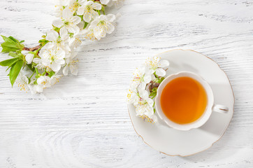 Cup of  tea and  branches of blossoming  cherry   on old  wooden  background.