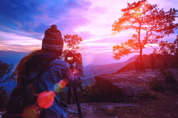 Asian women travel photograph nature. Travel relax. Photographer take a photo of the sun. On mountain cliffs. Thailand