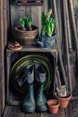 Old wooden workshop with clay pots and wellingtons