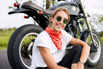 Cheerful relaxed female driver parks on road, poses against motorbike, sits on ground, has fun during driving, enjoys long route across beautiful landscapes outdoor. Travelling across world.