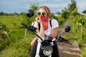 Attractive female in casual clothing, sits on motorbike, enjoys freedom and active lifestyle, has thoughtful expression, poses against green plantation backround outdoor. Motorcycle tourism concept
