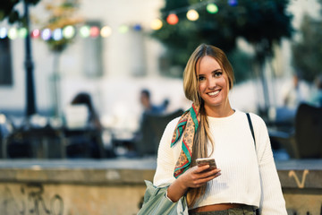 Woman with defocused urban city lights with smartphone.