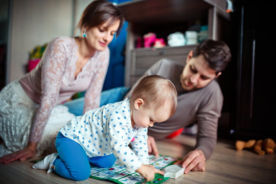 young parents play with their little daughter on the floor. Many toys.  happy family concept