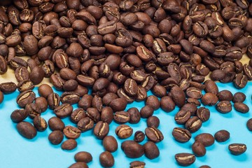 Roasted coffee beans on blue surface background