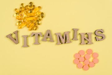 Vitamins And Supplements. Vitamin C, E. Background yellow, fish oil capsules and vitamin C vials