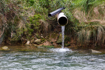 Water pouring from a drain pipe to the river, polluting the environment