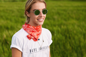Beautiful young female model in sunglasses wears casual white t shirt, red bandana on neck and shades, has walk across green field, being in good mood, enjoys sunshine and wonderful nature view