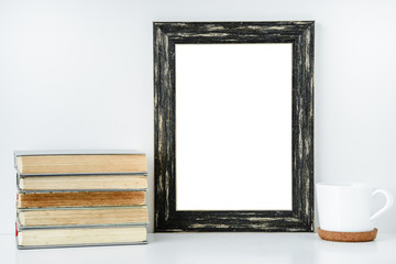 Black frame isolated with decorations from white cup and old books.