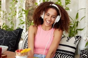 Happy female with dark healthy skin, listens anecdotes online with special application and headphones, laughes at funny joke, sits on comfortable sofa against cozy cafe interior. People and spare time