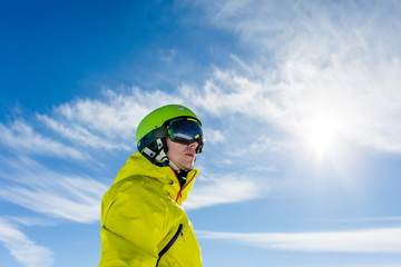 Photo of sporty man wearing mask and helmet against blue sky
