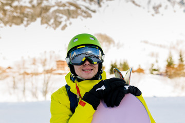 Image of sportive man wearing helmet with snowboard against background of snowy mountains