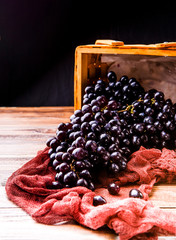 Picture of black grapes in wooden basket with claret cloth