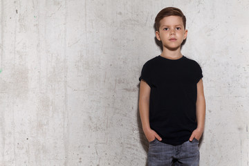 Cute little boy in black T-shirt posing in front of grunge concrete wall. Portrait of fashionable male child, copy space. Boy looks at camera, gray wall on background.