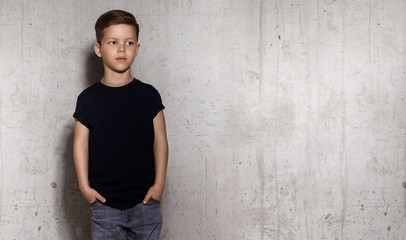 Wistful little guy stands on the wall background and looks away. Portrait of boy in black T-shirt, copy space. Concept of children style and fashion.