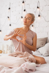 Portrait of a young beautiful fashionable blonde girl posing in home apartments. Woman makes gesture heart with fingers. Concept of Valentine's day and love. Modern bright home interior.