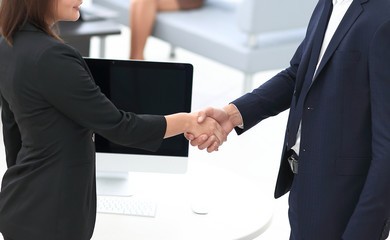 handshake business partners at the negotiating table.