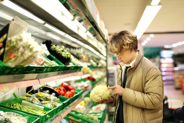 Young man buying vegetables at the market