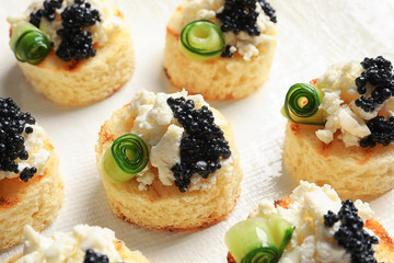Tasty black caviar appetizer on white background