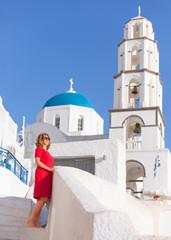 Barefooted woman in red dress enjoying the sun at Santorini island