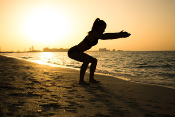 Silhouette of slim sporty girl exercising on the beach during sunset.