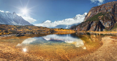 Wall Mural - Beautiful scene with high rocks with snow covered peaks, mountain lake, reflection in water, blue sky with clouds in sunset. Nepal. Panoramic landscape with mountains at bright sunny day. Himalayas