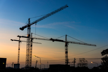 Silhouette of group of tower cranes in workplace. Building construction industrial in Thailand, Southeast Asia.