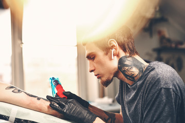 A young guy, beats a tattoo on the hand of the girl in a tattoo parlor, rotary tattoo machine, black ink, lens flare, close up