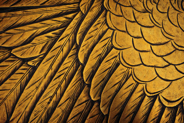 Section of an eagle's wing on a golden metal plaque.