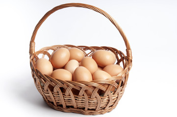 vintage basket full of hen eggs over white isolated background like Easter or bio farm meal concept
