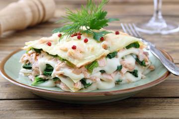 lasagne al forno con salmone e spinaci su sfondo rustico