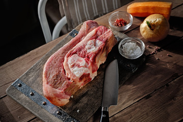 Raw beef with bone on wooden board and table. Beef-infusion broth ingredients. With knife, salt and pepper.