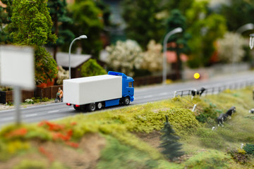 Model or model of a blue truck with a white van-body goes on the road rural landscape. Model truck on the asphalt road. The effect of tilt shift