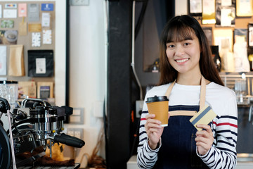 Young asian woman barista holding a disposable coffee cup and credit card with smiling face at cafe counter background, small business owner, food and drink industry concept