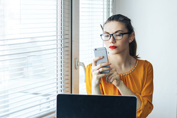 women in glasses sitting near window near computer looking at mobile phone