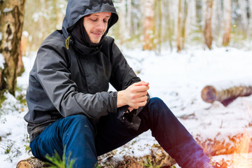 Man traveler in the forest sits on a log in the winter and looks at the fire