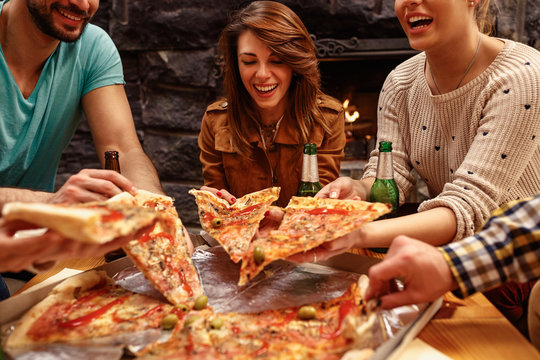 laughing friends eating pizza and having fun. They are enjoying eating and drinking together