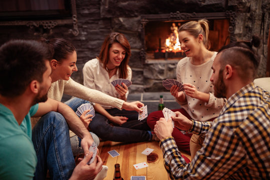 Smiling friends partying together and playing cards