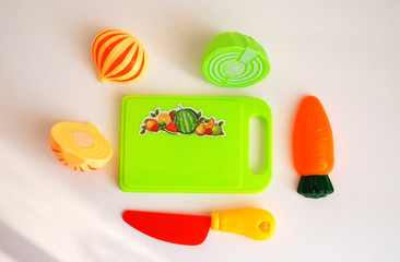 children's toy set, plastic multicolored fruits and vegetables, on a green board