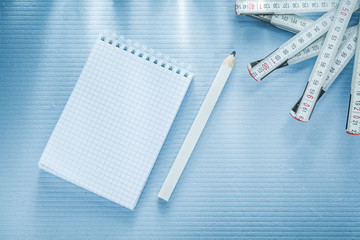 Checked notepad pencil tape measure construction concept