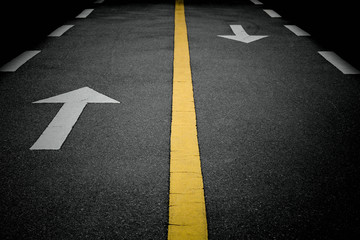 white forward arrow signs on the road