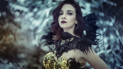 Queen, Beautiful brunette woman with gothic dress made in gold and black threads. It is in a snowy forest in winter. fantasy concept