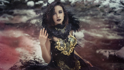 Beautiful brunette woman with gothic dress made in gold and black threads. It is in a snowy forest in winter. fantasy concept