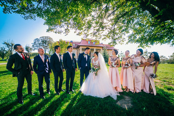 Newlywed couple, bridesmaids & groomsmen having fun outdoors. Bride and groom with best friends posing at sunny green park. Summer picture.