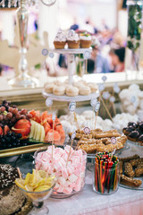 luxury wedding catering, table with modern desserts, cupcakes, sweets with fruits. delicious candy bar at rich wedding reception. space for text. shower. holiday celebration