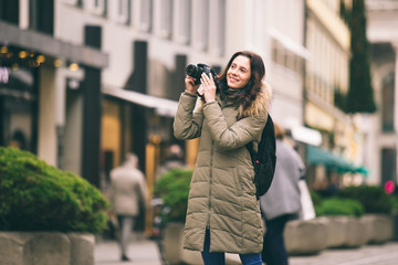 Beautiful young tourist woman stands on the background of the central street in Munich in Germany in winter. Holds a black big professional camera, takes a photo and smiles.