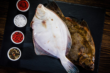 Raw flounder with herbs served on black stone on wooden table