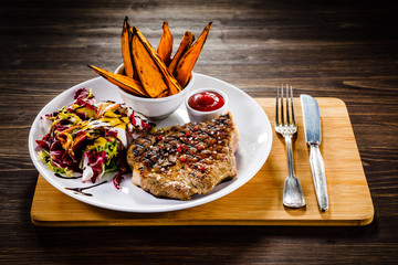 Grilled beefsteak with baked sweet potatoes ad vegetable salad on wooden table