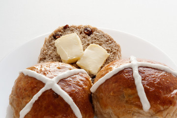Good Friday. Hot Cross Buns with raisins and butter on a white bowl. Easter. Bakery. Food.