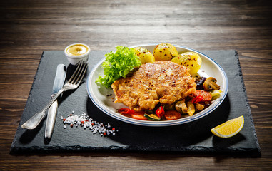 Fried pork chop with potatoes served on black stone